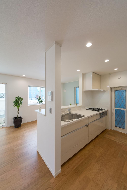 白を基調とした清潔感あるキッチン。キッチン扉は白系の木目調です。