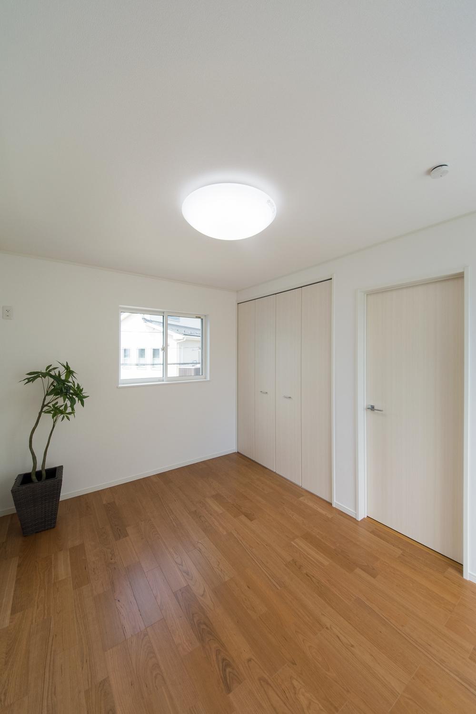 白のクロスとブラックチェリーのフローリングがナチュラルな雰囲気を演出する2階洋室。