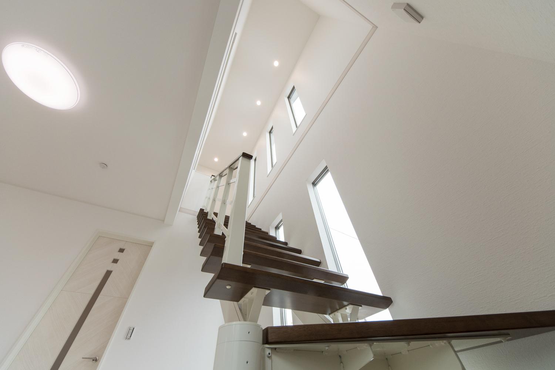 吹抜けに面した3連窓から光が差し込む、とても明るいオープンスタイルの階段。