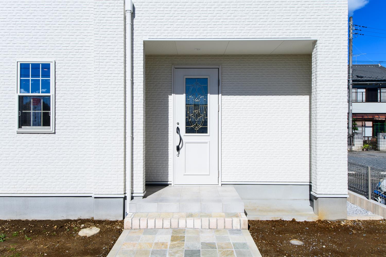 白い外壁に、上部に大きなガラスを配したフレンチテイストの白い玄関ドアがお迎えします。