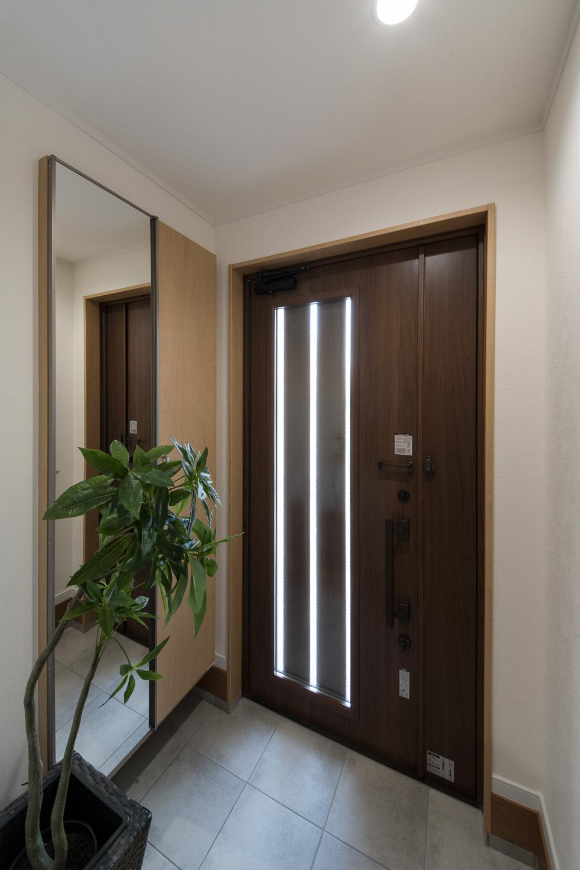 ナチュラルな配色の玄関。ドアの縦スリットとから自然の光が差し込みます。