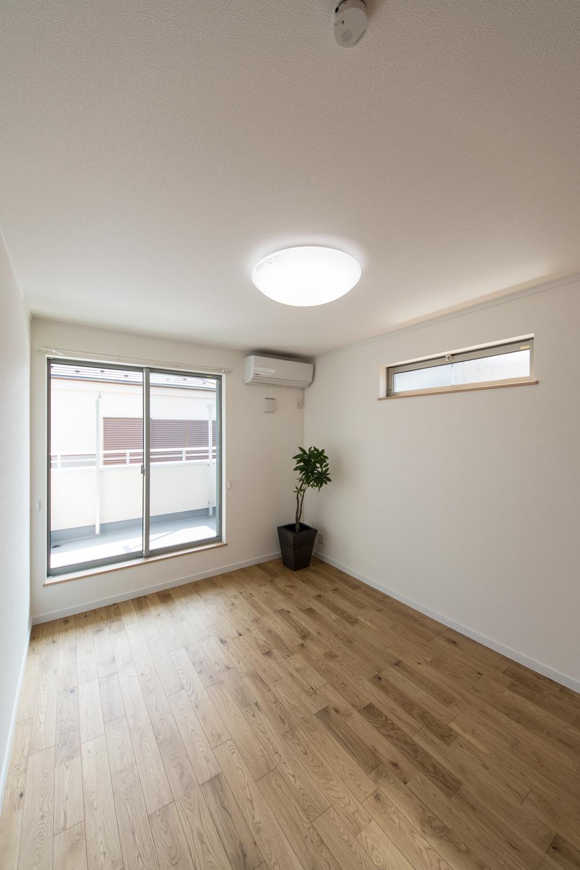 大きな窓と横長のデザイン窓から自然のやさしい光が降り注ぐ2階洋室。