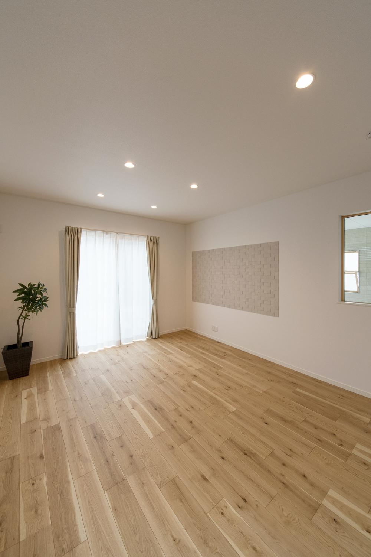 大きな窓から自然のやさしい光が降り注ぐ、明るく開放的なリビング。愛車を眺める室内窓も施しました。