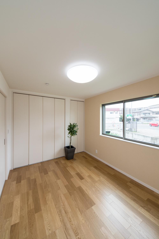 1F洋室/温かみのある色のクロスがお部屋のアクセントになっています。