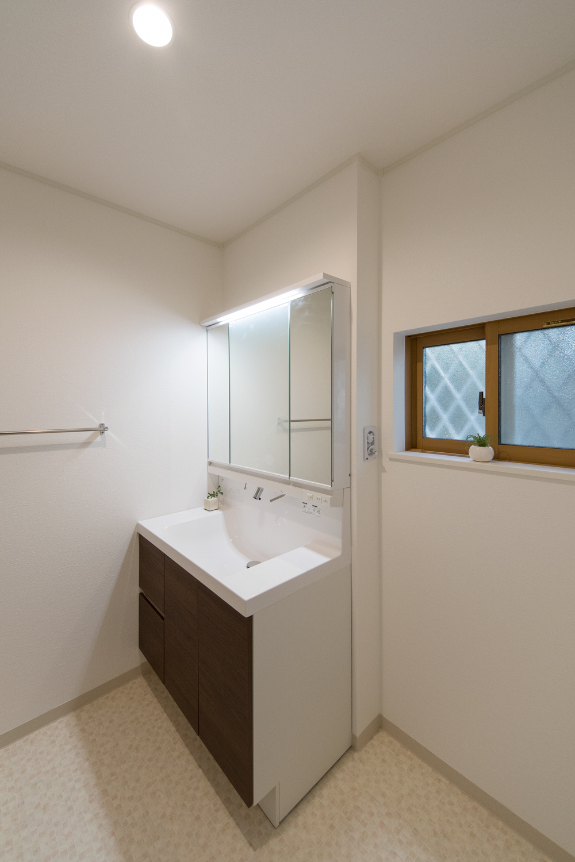白を基調とした清潔感のあるサニタリールーム。洗面化粧台扉をブラウンでアクセントに。