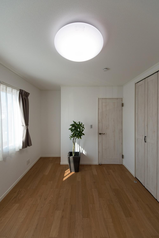 シャビーシックなデザインの白い木目調建具をアクセントにした2階洋室。