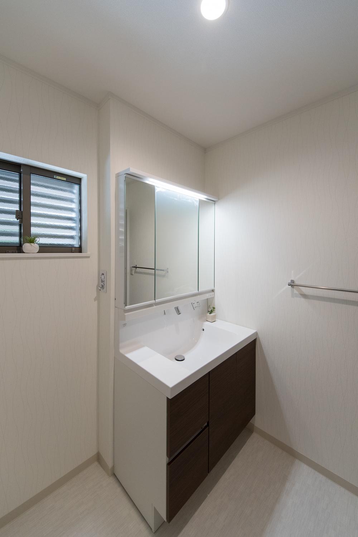 白を基調とした清潔感のあるサニタリールーム。洗面化粧台扉をダークブラウンでアクセント。