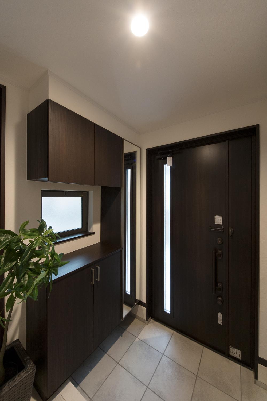 玄関ドア・玄関収納をモノトーンカラーで差し色にしたシックで大人な雰囲気の玄関。