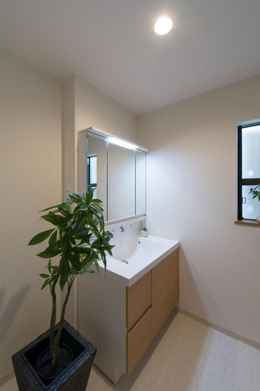 白を基調とした清潔感のあるサニタリールーム。洗面化粧台扉を木目柄でアクセントに。