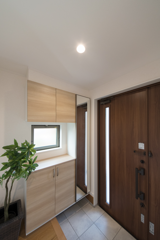 ドアの縦スリットと窓から自然の光が差し込む明るい玄関。