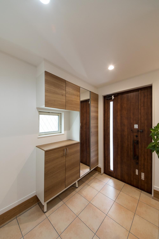 ドアの縦スリットと窓から自然の光が差し込む明るく広々とした玄関。