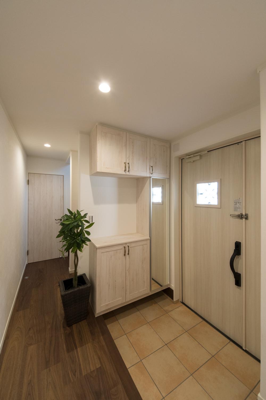 シャビーシックな白い玄関扉とベージュのテラコッタ調タイルがアンティークな風合いを演出。