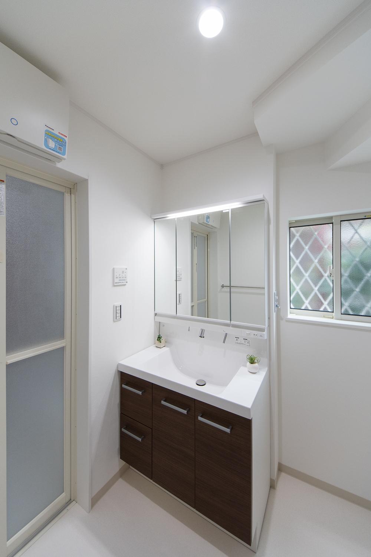 白を基調とした清潔感のあるサニタリールーム。木目調の洗面化粧台がナチュラルな雰囲気を演出。