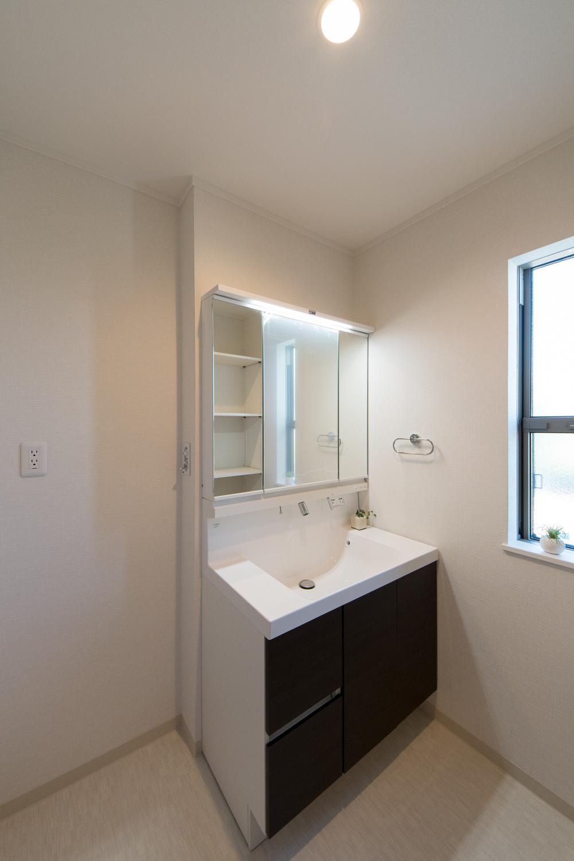白を基調とした清潔感のあるサニタリールーム。木目調の洗面化粧台がナチュラルな雰囲気を演出