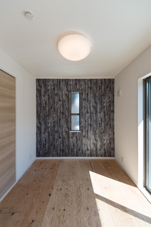 1階畳敷き洋室(写真は畳設置前)/黒の濃淡がカッコイイ、進化したデザインの木目柄クロスをアクセントにしました。