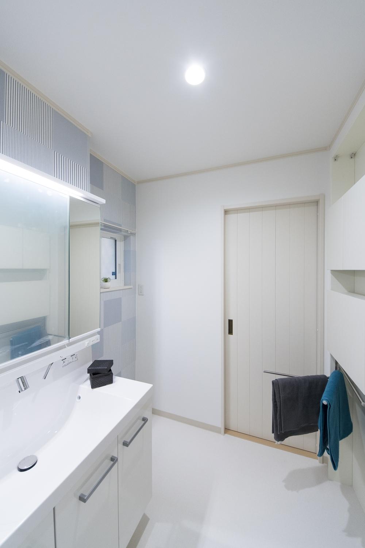壁を利用した機能的な薄型キャビネットを設置。洗面室とキッチンの間にもドアを設け、家事動線の良い2Wayの間取り。