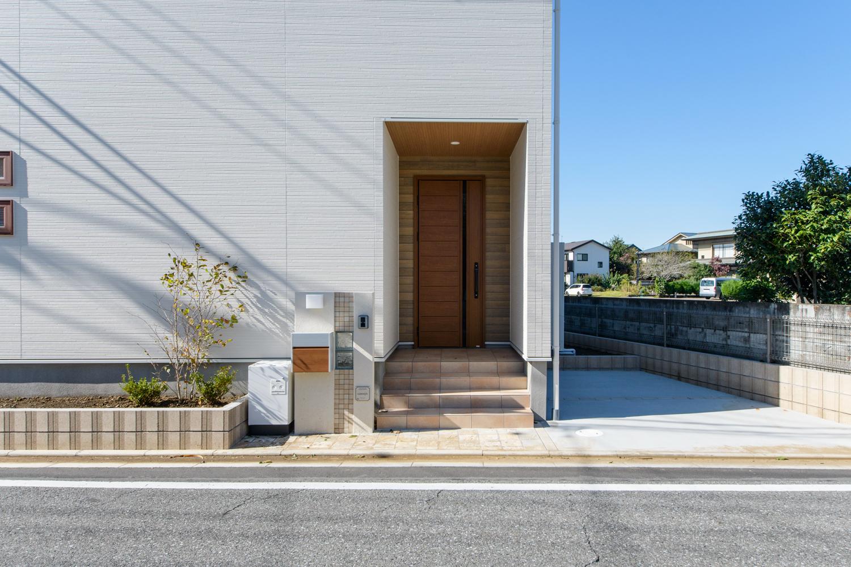 白をベースに玄関周りに木目調のサイディングをアクセンとにしたナチュラルテイストな外観。