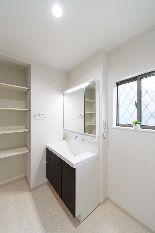 白を基調とした清潔感のあるサニタリールーム。洗面化粧台扉をダークブラウンでアクセントに。