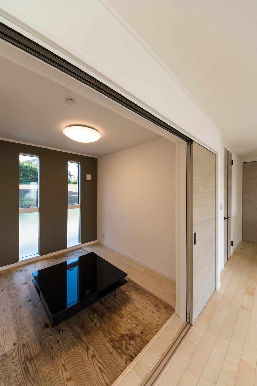 1階畳敷き洋室(写真は畳設置前)/シックな配色のアクセントクロスと二連の縦窓を施したモダンな和空間。