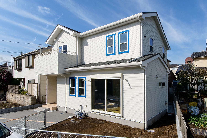 白い外壁をベースにブルーの窓モールでアクセントを付けた、爽やかで温かみのあるカリフォルニアスタイル。