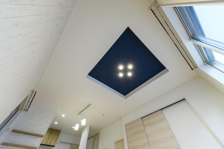 優雅な雰囲気を醸し出す折り上げ天井のリビング。ネイビーのクロスを施し、ダウンライトをダイヤ型に並べました。