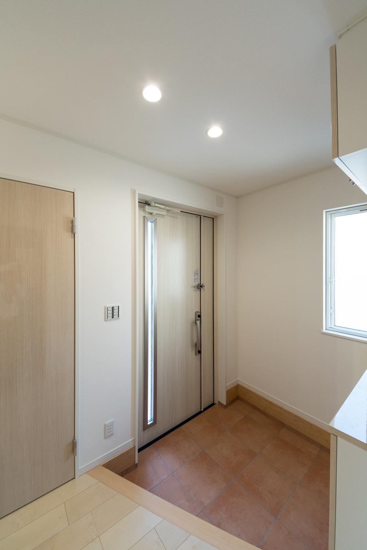 白木調の玄関扉と、赤みのあるカラーのテラコッタ調タイルがナチュラルで温かな雰囲気を演出。