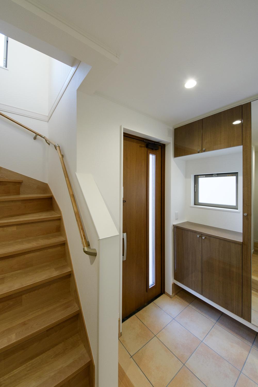 木の温もり感じるナチュラルテイストな玄関。窓からたっぷりと自然光が差し込む明るい空間。