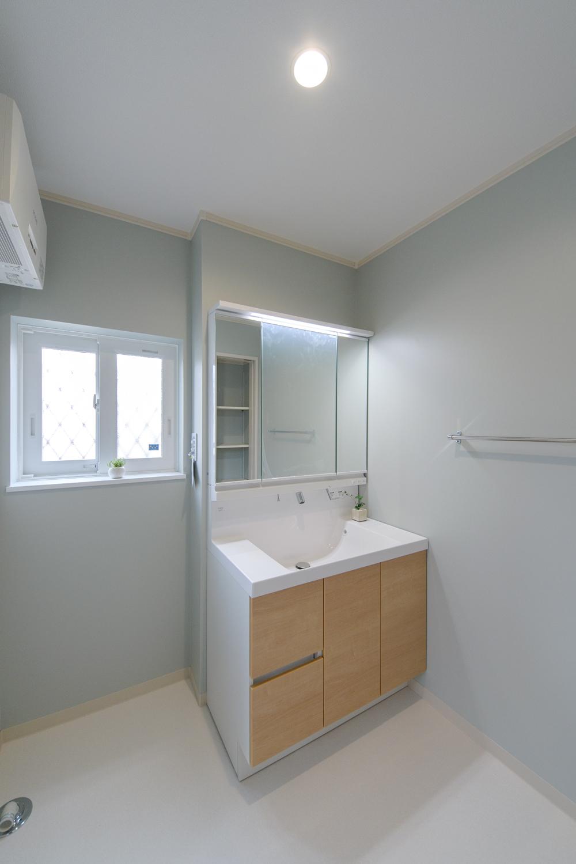 淡いグリーンのクロスが爽やかな印象のサニタリールーム。木目調の洗面化粧台扉がアクセントです。