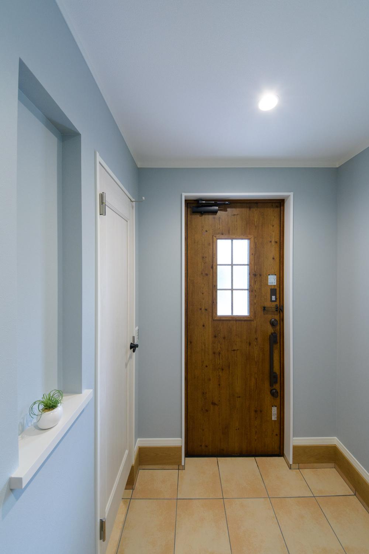 淡いブルーを基調に、白や木目調でアクセントをつけたカリフォルニアテイストのおしゃれな玄関。