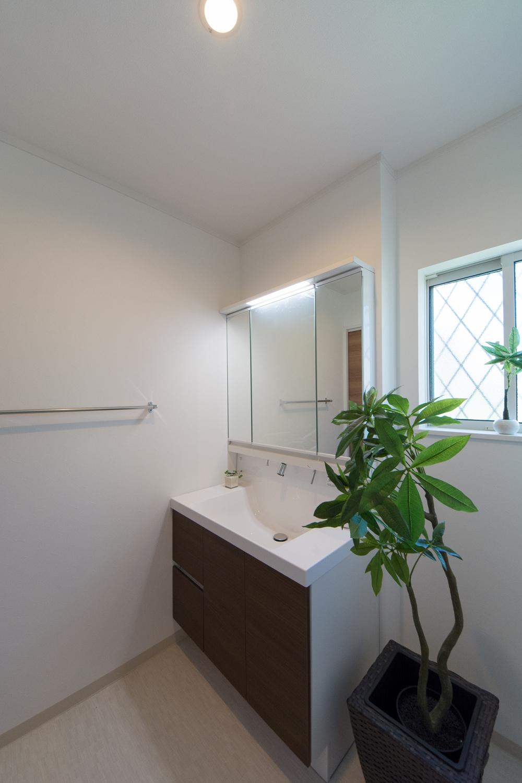 白を基調とした清潔感のあるサニタリールーム。洗面化粧台扉をモカ色でアクセント。