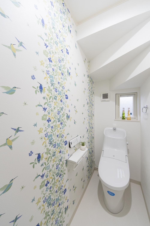 1階トイレ/鳥と花をモチーフにしたカラフルなクロス。階段のフォルムもデザインの一部に見える素敵な仕上がりに。
