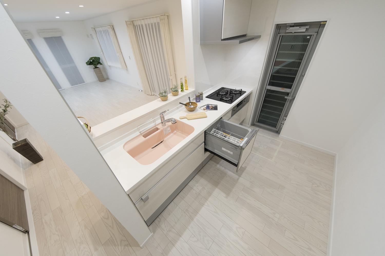 パステルカラーのシンクをアクセントにした明るく可愛らしい印象のキッチン。食器洗い乾燥機を施し機能美も充実。