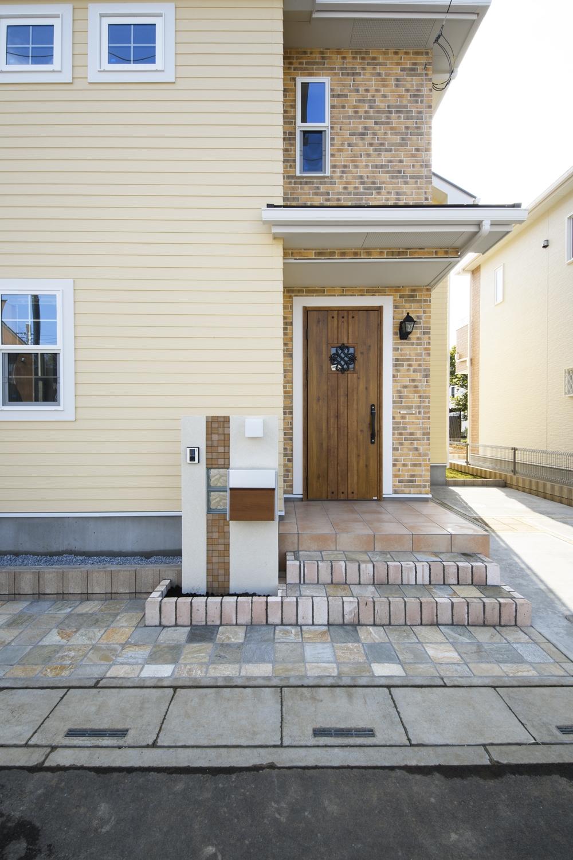 玄関周りにブリック調サイディングでアクセントをつけ、ドアに鋳物飾りを施した、エレガントなデザインの玄関。