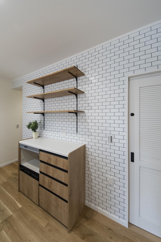 白いレンガを表現した壁紙に映える、手仕事感のあるラフな木目のカウンターとカップボード。