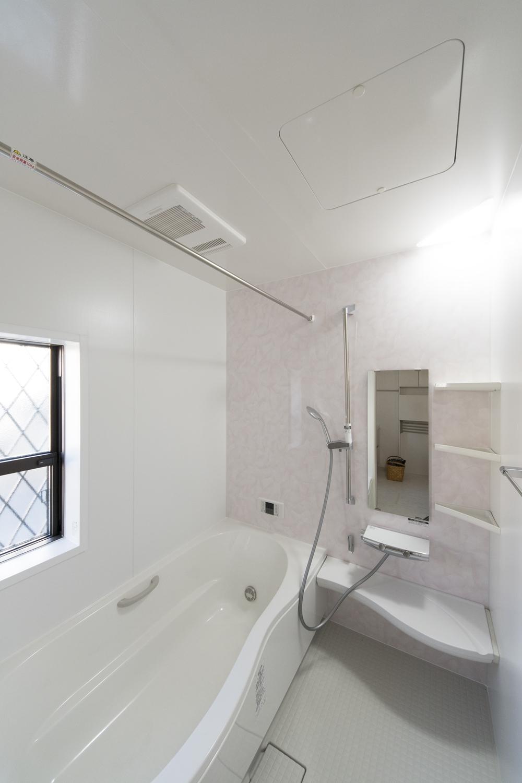 淡いピンクのパターン柄アクセントパネルが明るく柔らかい雰囲気のバスルームを演出。
