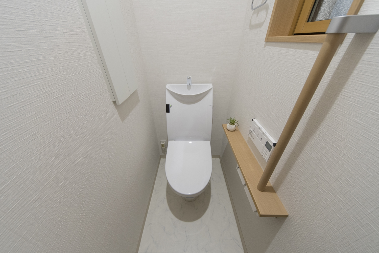 1階トイレ/白を基調とした清潔感のある内装。手すりを設置して安全で快適な暮らしをサポート。