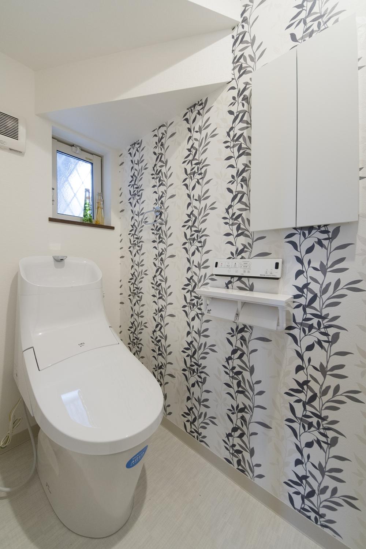 1階トイレ/ナチュラルなリーフ柄をシックなカラーで表現したアクセントクロスが心地よい空間を演出。