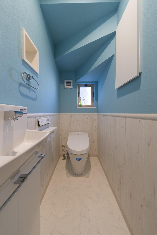 鮮やかな水色と白木調のクロスを上下に張り分けたスタイリッシュな1階トイレ。
