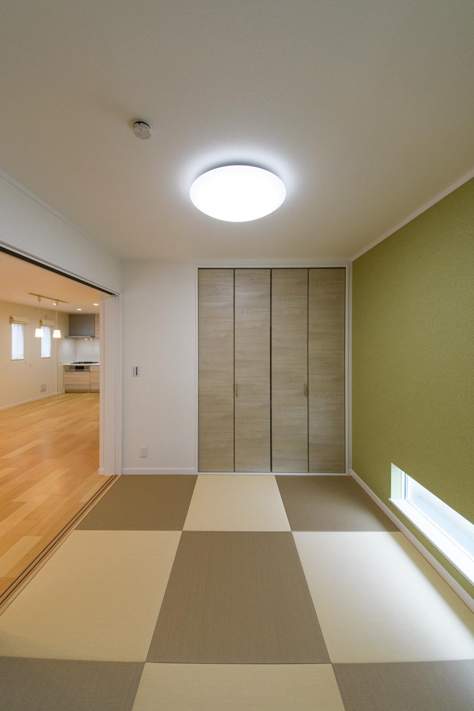 1階畳敷き洋室/抹茶色の壁紙を貼り、モカベージュとアイボリーの畳をダミエ模様に並べた、オシャレでモダンなスペース。