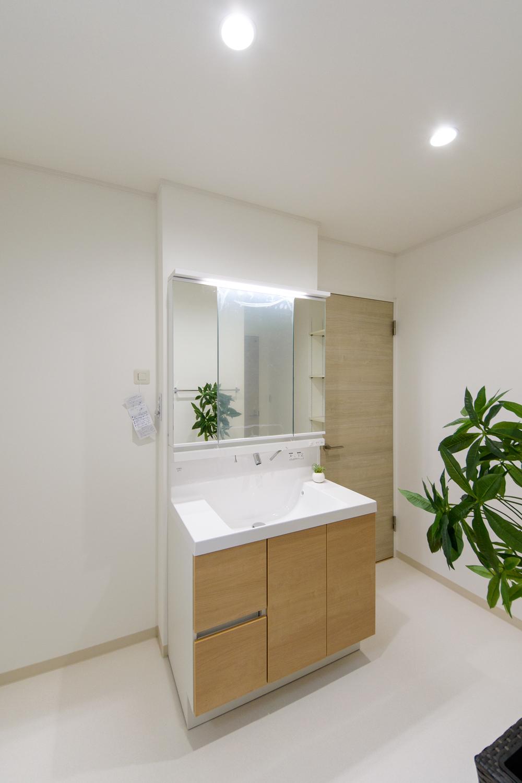 白を基調とした清潔感のあるサニタリールーム。洗面化粧台扉を明るい木目調カラーでアクセント。