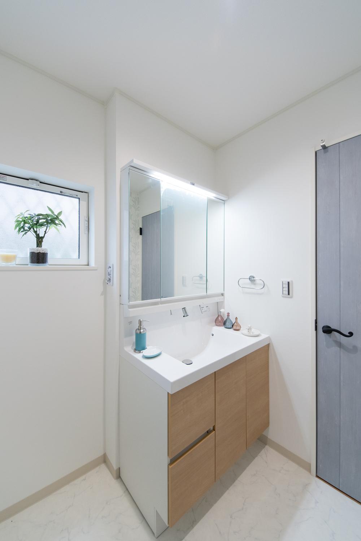 清潔感のあるサニタリールーム。洗面化粧台扉を明るい木目調カラーでアクセント。