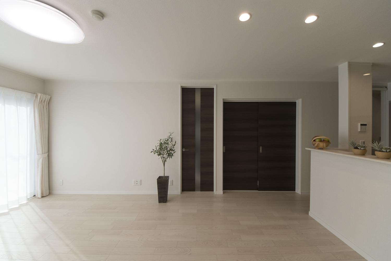 白をベースにモノトーンカラーの建具を差し色にした、シックで大人な雰囲気のリビング。