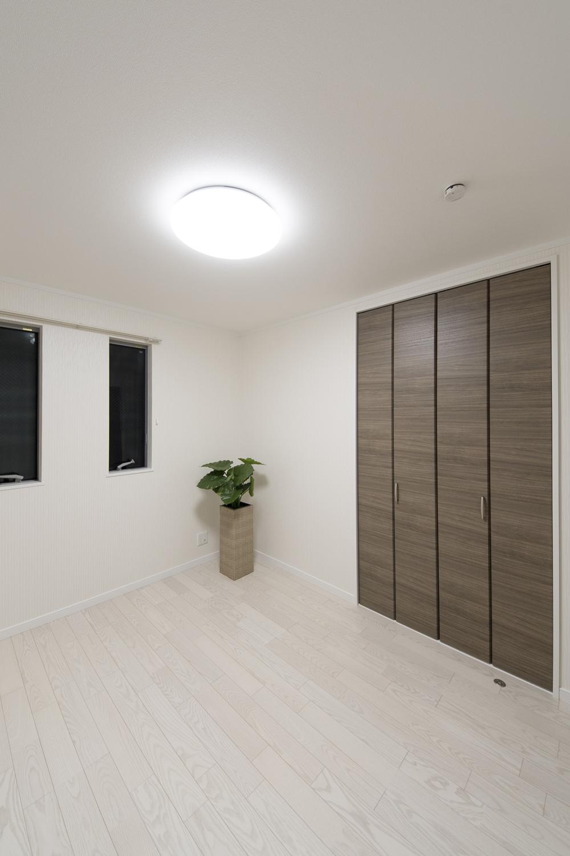 白い空間に、ダークブラウンの建具をアクセントにしたコントラストの美しい2階洋室。