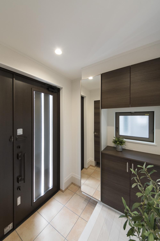 ダークブラウンのドアと収納が玄関スペースに深みを与え、ドアの縦スリットと窓から自然の光が差し込みます。