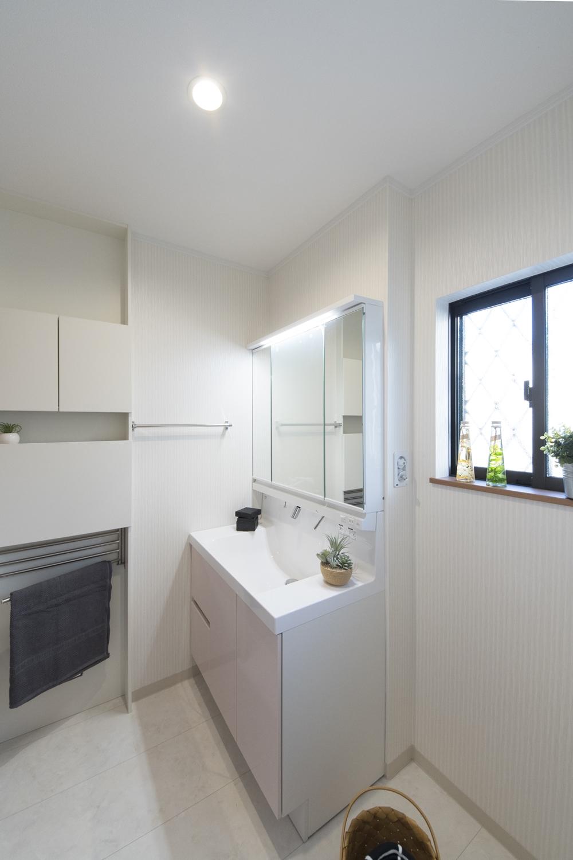 パステルピンクの洗面化粧台が可愛らしい印象のサニタリールーム。壁を利用した機能的な薄型キャビネットを設置。