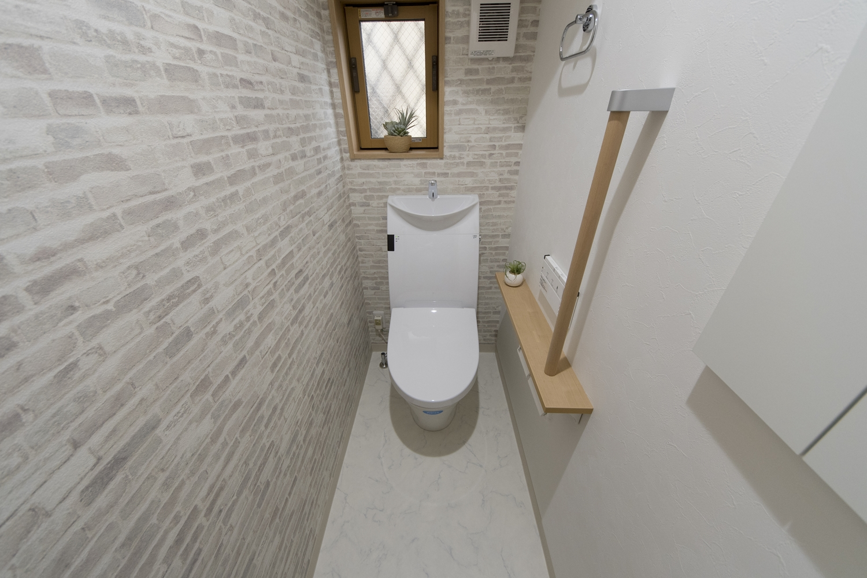 1Fトイレ/レンガ調のアクセントクロスを2面に貼ったオシャレな空間。手すりを設置して安全で快適な暮らしをサポート。