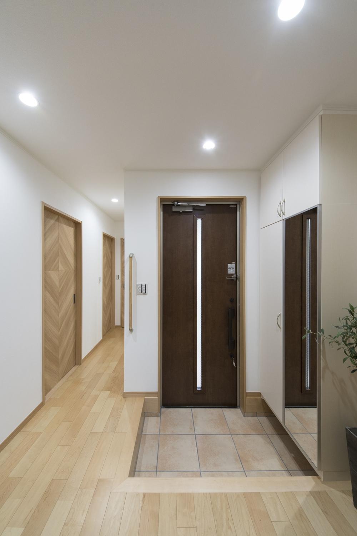 1F玄関(子世帯)木の温もり感じる玄関ドアとベージュのテラコッタ調タイルが穏やかな空間を演出。