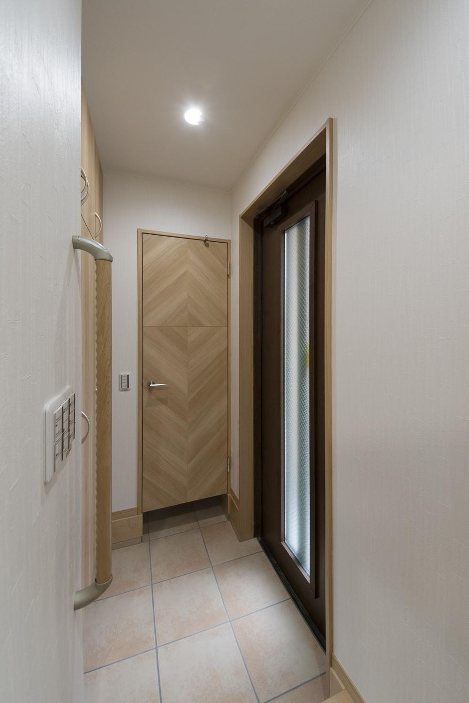 1F玄関(親世帯)/木の温もり感じるナチュラルな配色。昇り降りをやさしくサポートする手摺を設置しました。