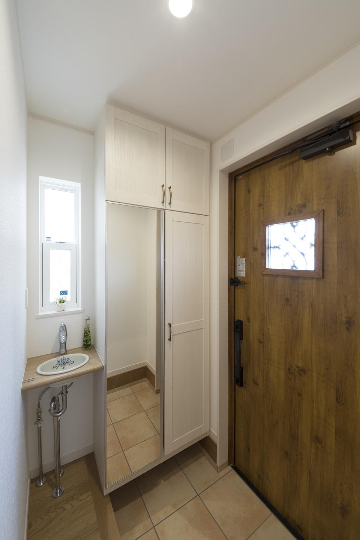 お洒落なデザインの丸型手洗いキャビネットを玄関脇に設置しました。
