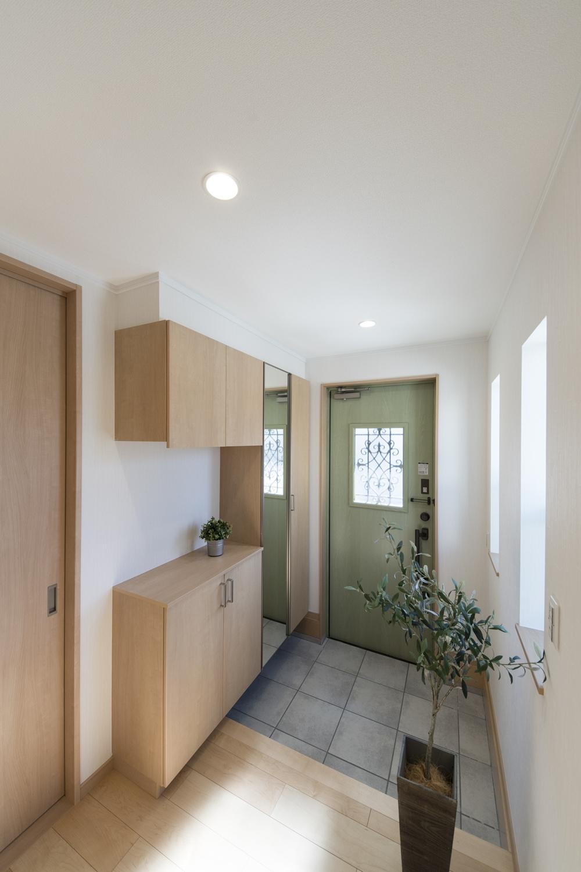 2世帯共有の玄関/爽やかなグリーン色のドアが空間を彩り、木の温もり感じる木目調の収納が玄関をナチュラルな雰囲気に包みます。